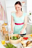 Glowing young woman preparing salad at home