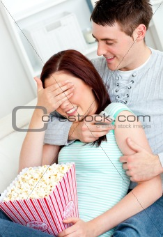 Charming couple lying on the sofa with popcorn and remote