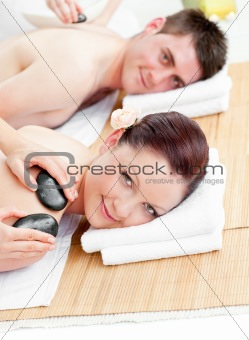 Attractive young couple receiving a back massage with hot stones