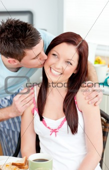Attentive boyfriend kissing his girlfriend at her cheek during b