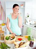 Glowing young woman tasting her salad at home