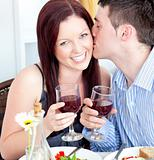 Happy boyfriend kissing his beautiful girlfriend during dinner