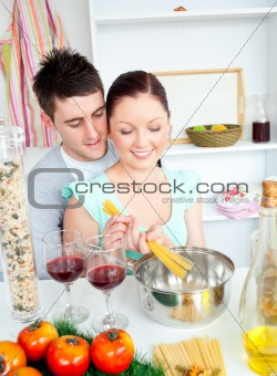Caucasian young couple cooking spaghetti in the kitchen