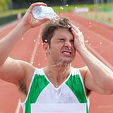 Young sprinter spraying water on his head
