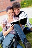 Smiling couple of students reading a book sitting on grass