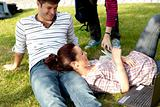 Couple of bright students lying on the grass
