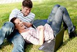 Couple of bright students using a laptop lying on the grass