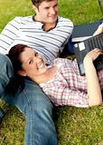 Couple of cheerful students using a laptop lying on the grass