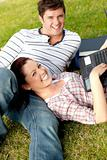 Couple of happy students using a laptop lying on the grass