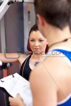 Assertive athletic woman using a bench press with her coach