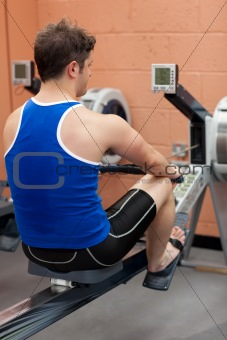 Athletic caucasian man using a rower