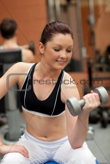 Portrait of a positive woman working out with dumbbells