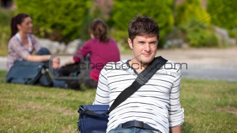 Positive male student lying on the grass with his schoolbag
