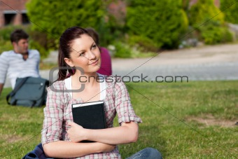 Thoughtful female student reading a book sitting on grass