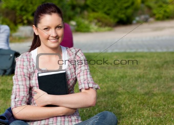 Positive female student holding a book sitting on grass