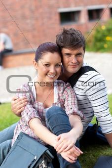 Beautiful couple of students sitting on grass and smiling at the