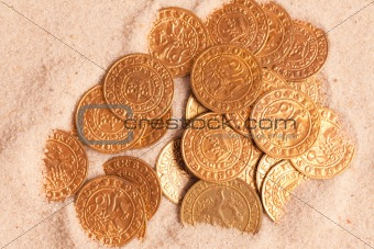 old golden coins in sand