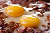 closeup of two eggs and bacon in a pan