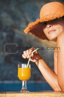 Attractive woman in hat with glass of orange juice