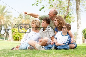 potrait of grandfather pointing with family