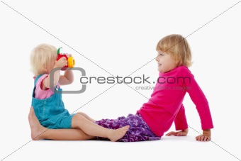sisters taking pictures of each other with toy camera - isolated on white