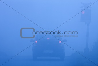 car waiting at rural railroad crossing with red lights blinking in fog
