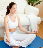 Young woman sitting on the floor doing yoga