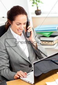 Busy businesswoman talking on phone and using her laptop sitting
