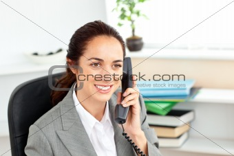 Attractive businesswoman talking on phone sitting in her office