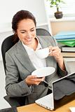 Smiling businesswoman holding a coffee while using a laptop at w