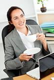 Businesswoman holding a cup of coffee in front of her laptop sit