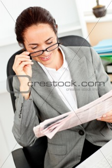 Bright businesswoman holding glasses and looking the newspaper