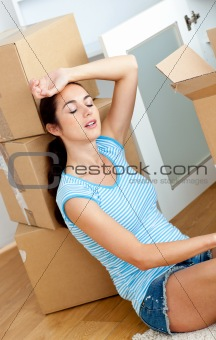 Tired woman sitting on the floor after unpacking boxes