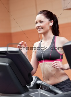 Smiling athletic woman training on a running machine with earpho