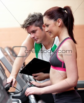 Beautiful athletic woman standing on a running machine with her
