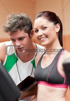 Smiling athletic woman standing on a running machine with her personal coach
