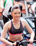 Smiling young woman training on a bicycle in a fitness center