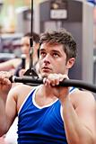 Muscular male athlete practicing body-building in a fitness center