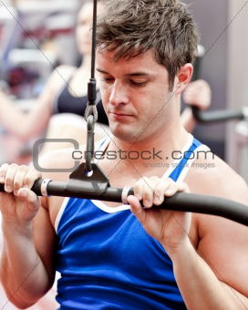 Beautiful male athlete practicing body-building