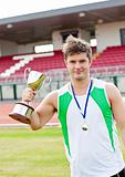 Delighted male athlete holding a cup and a medal standing