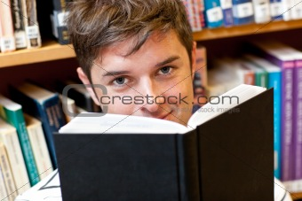 Portrait of a good-looking male student reading a book sitting o