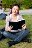 Bright female student reading a book sitting on the grass