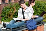 Couple of students using a laptop and reading a book sitting