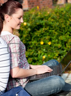 Charming female student using a laptop and sitting behind her bo