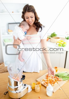 Caring young mother preparing vegetables for her baby in the kit