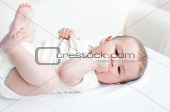 Adorable baby lying on the back in the living-room