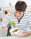 Delighted young man eating a healthy salad in the kitchen