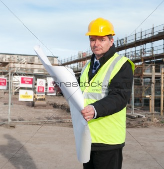 Architect on building site looks at camera