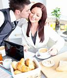 Attractive businessman kissing his bright girlfriend during breakfast