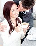 Handsome businessman kissing his girlfriend who is holding a cup